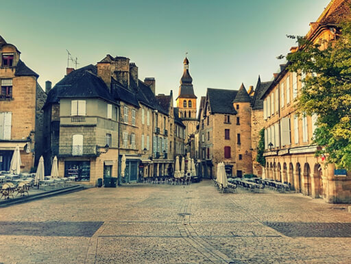 Historic buildings in Place de la Liberté in Sarlat, France, on a partly cloudy day.
