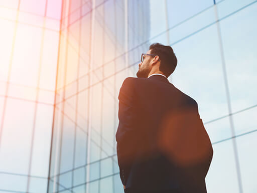 A businessman looks toward the sky next to a tall office building during his lunch break.