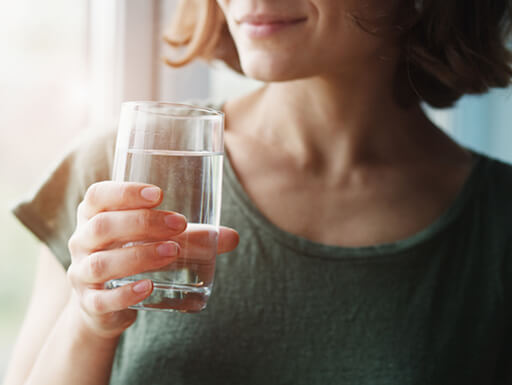A woman drinks 16 ounces of water first thing in the morning.