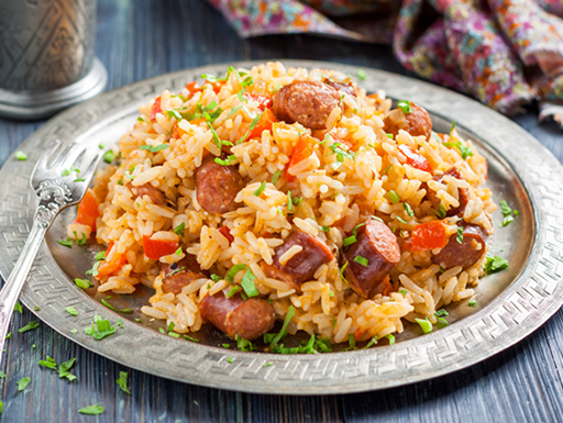 A close-up image of a warm plate of Jambalaya with sausage and seafood on a plate during lunchtime.
