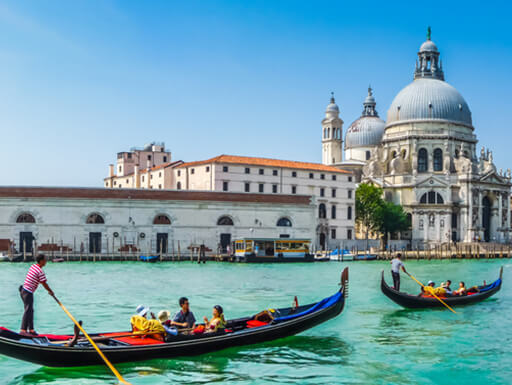 Traditional gondolas on the Grand Canal in Venice, with the Basilica di Santa Maria Della Salute in the background