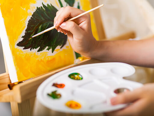 An up-close image of a woman's hand holding a paint brush and palette of colors as she paints a green leaf with a yellow background