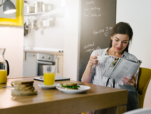A woman starts her day on the right foot by eating a healthy breakfast and reading the newspaper.