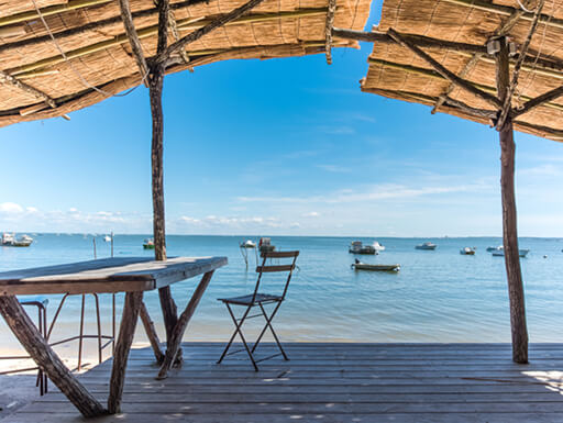 View of the beach and clear ocean water in Arcachon Bay, France with tan shade coverings and seating in the forefront.