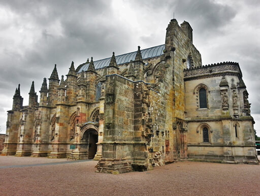 An exterior view of the striking Rosslyn Chapel on a grey stormy day.