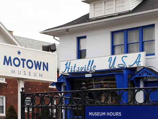 """The exterior signs of the Motown Museum in Detroit, MI sit beneath a cloudy sky on an overcast afternoon."