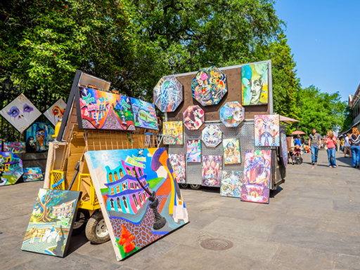 Colorful paintings by local New Orleans artists are on display in Jackson Square as tourists explore the area on a bright afternoon.
