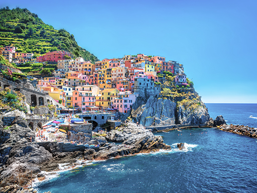 Colorful houses perch on a dramatic clifftop in the Cinque Terre region of the Italian Riviera