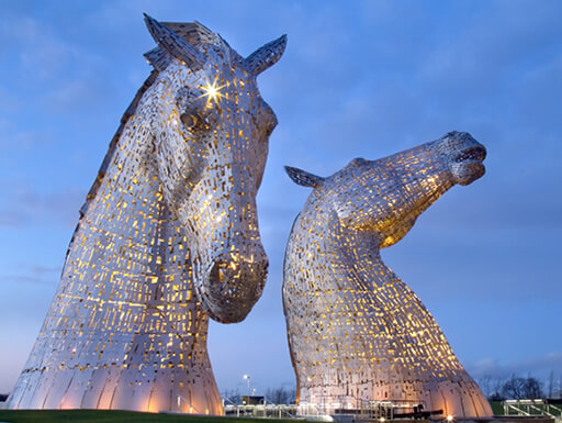 A photo taken of the illuminated Equine statues as evening arrives.