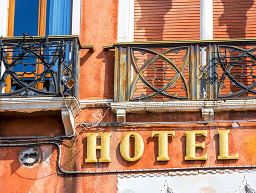 Orange-hued façade of a hotel with vintage balcony and window