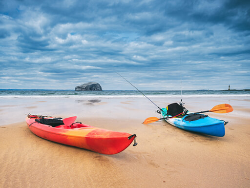 Two colorful kayaks sat on the golden shores on North Berwick.