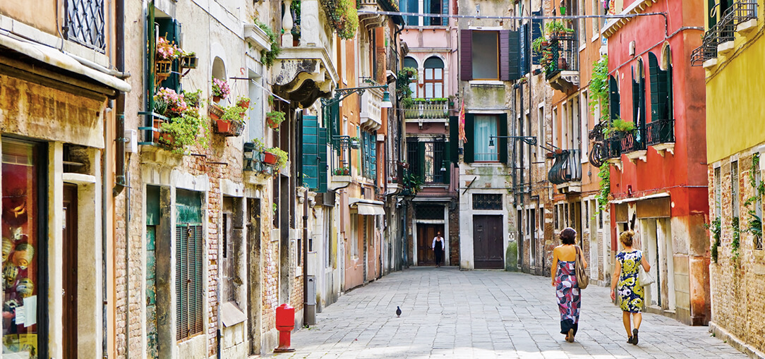 A view of colorful Venetian houses with some visitors walking by in Venice, Italy