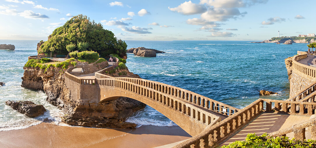 A brown stone bridge crossing blue ocean water to a small island near Biarritz, France with lush greenery on a sunny day.