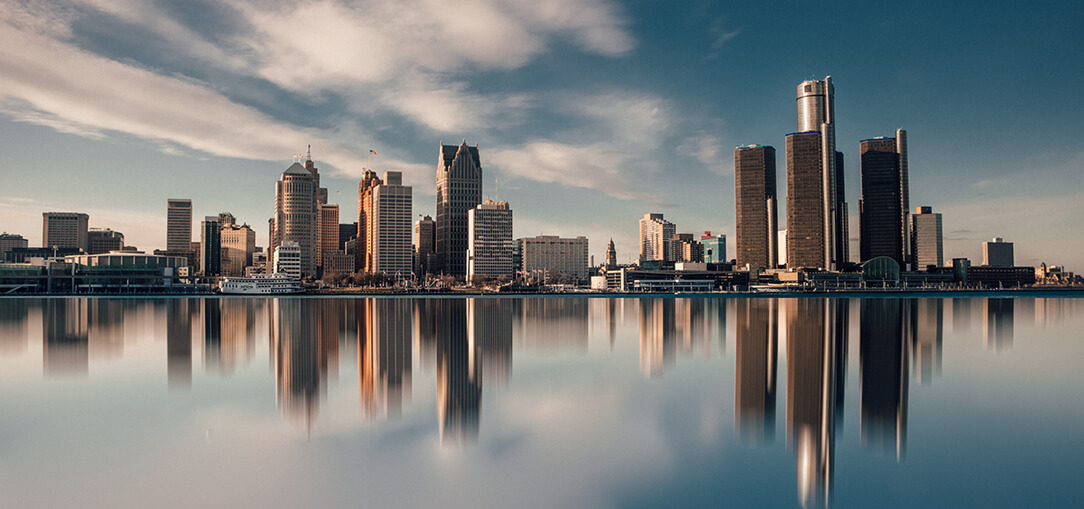 Detroit's downtown skyline shines beneath the sunlight as its reflection hits the water on a bright afternoon.