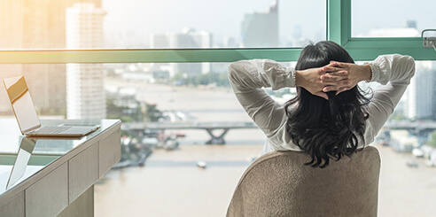A businesswoman takes 30 seconds to relax as she looks out of the office window on a bright afternoon.