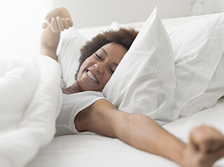 A woman wakes up in bed and stretches her arms with a smile on her face.