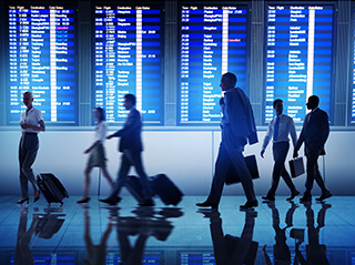 Various groups of people carrying luggage pass by the blue illuminated Travel Departure Board at an airport on an early morning.