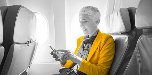 A woman sits in the window seat of an airplane and checks her Hertz reservation on her phone before takeoff.