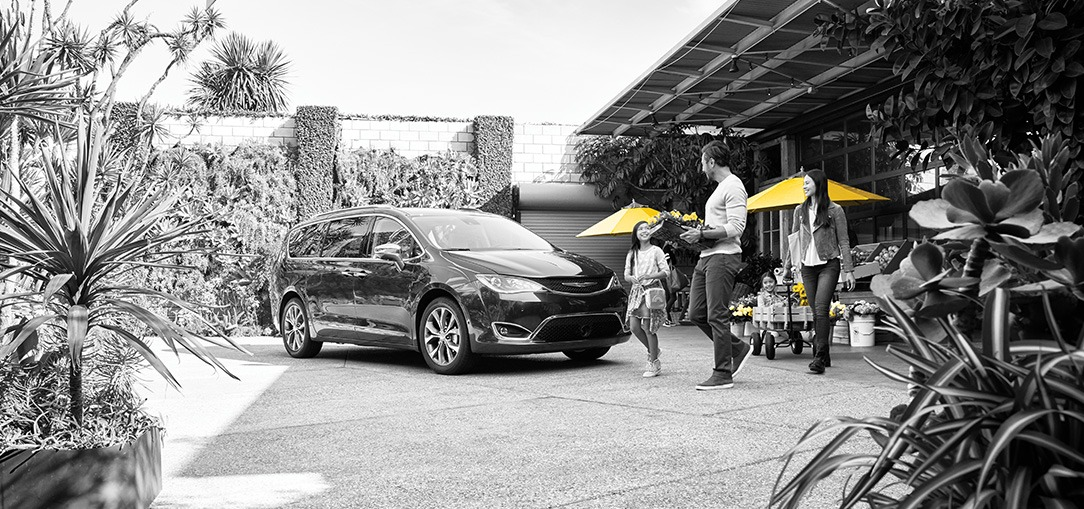 A father, mother, and their young daughter walk to their black minivan rental vehicle in front of a plant store.
