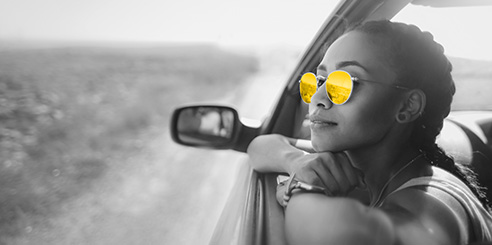 A woman in her twenties wears sunglasses as she sits in her parked vehicle and looks out the window.