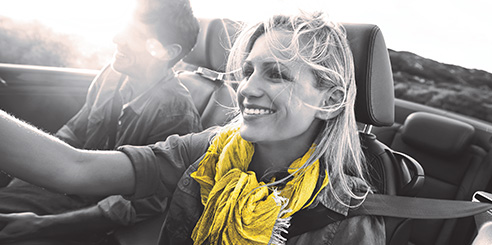 A blonde woman smiles as she drives a Hertz convertible rental car with her husband on a bright afternoon.